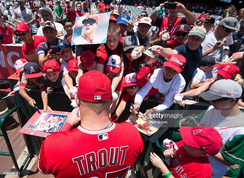 <a gi-track='captionPersonalityLinkClicked' href=/galleries/search?phrase=Mike+Trout&family=editorial&specificpeople=7091306 ng-click='$event.stopPropagation()'>Mike Trout</a> #27 of the Los Angeles Angels of Anaheim signs autographs for fans before the game against the Oakland Athletics at Angel Stadium of Anaheim on June 26, 2016 in Anaheim, California.