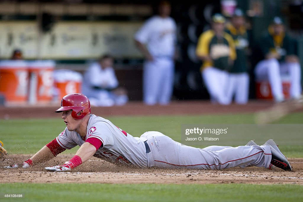 Mike Trout #27 of the Los Angeles Angels of Anaheim slides head first into home plate to score a run against the Oakland Athletics during the fourth inning at O.co Coliseum on August 24, 2014 in Oakland, California.