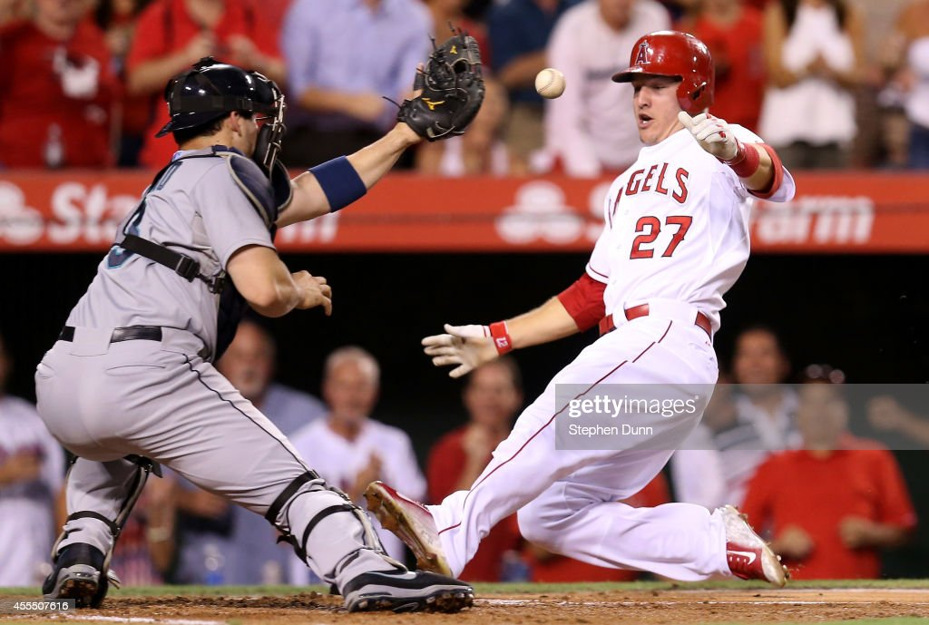 <a gi-track='captionPersonalityLinkClicked' href=/galleries/search?phrase=Mike+Trout&family=editorial&specificpeople=7091306 ng-click='$event.stopPropagation()'>Mike Trout</a> #27 of the Los Angeles Angels of Anaheim slides home ahead of the throw to catcher <a gi-track='captionPersonalityLinkClicked' href=/galleries/search?phrase=Mike+Zunino&family=editorial&specificpeople=6803368 ng-click='$event.stopPropagation()'>Mike Zunino</a> #3 of the Seattle Mariners with the third run of Albert Pujols' three run double in the third inning at Angel Stadium of Anaheim on September 15, 2014 in Anaheim, California.