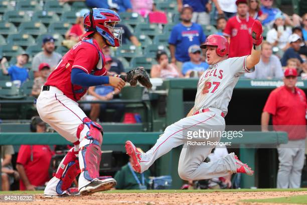 Mike Trout of the Los Angeles Angels of Anaheim slides home to score on a double by Andrelton Simmons in the 9th inning as Robinson Chirinos of the...