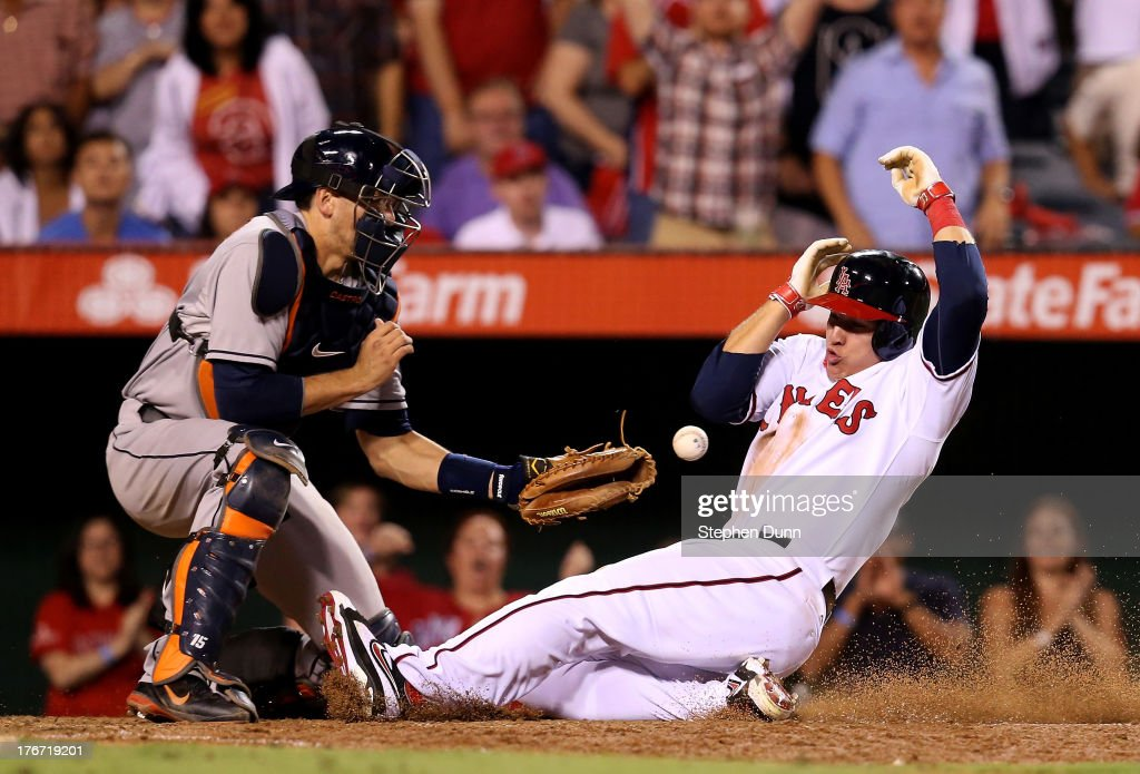 Mike Trout of the Los Angeles Angels of Anaheim slides home with the tying run in the seventh inning as catcher Jason Castro of the Houston Astros...