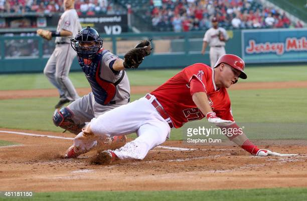 Mike Trout of the Los Angeles Angels of Anaheim slides in past the attempted tag of catcher Kurt Suzuki of the Minnesota Twins to score the second of...