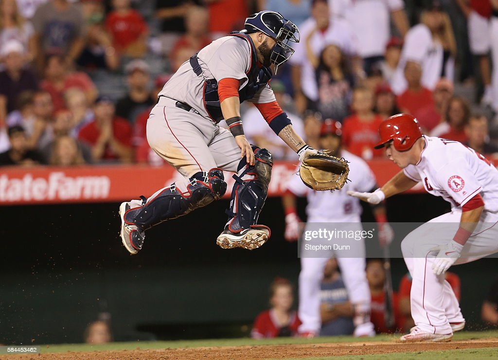 Mike Trout #27 of the Los Angeles Angels of Anaheim slides past catcher Sandy Leon #3 of the Boston Red Sox to score the tying run in the ninth inning after Leon jumped but couldn't reach the ball on a throwing error at Angel Stadium of Anaheim on July 28, 2016 in Anaheim, California. The winning run also scored on the play as the Angels won 2-1.