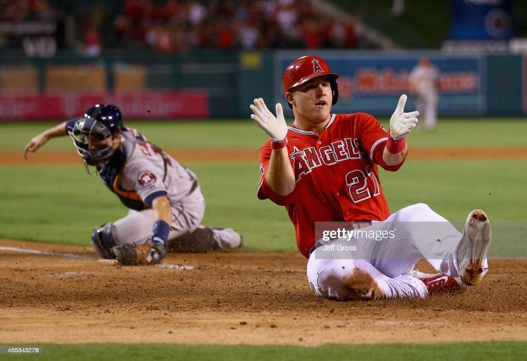 <a gi-track='captionPersonalityLinkClicked' href=/galleries/search?phrase=Mike+Trout&family=editorial&specificpeople=7091306 ng-click='$event.stopPropagation()'>Mike Trout</a> #27 of the Los Angeles Angels of Anaheim slides safely past catcher Jason Castro #15 of the Houston Astros and scores a run on a catching error by shortstop Jonathan Villar (not pictured) in the fourth inning at Angel Stadium of Anaheim on September 12, 2014 in Anaheim, California.