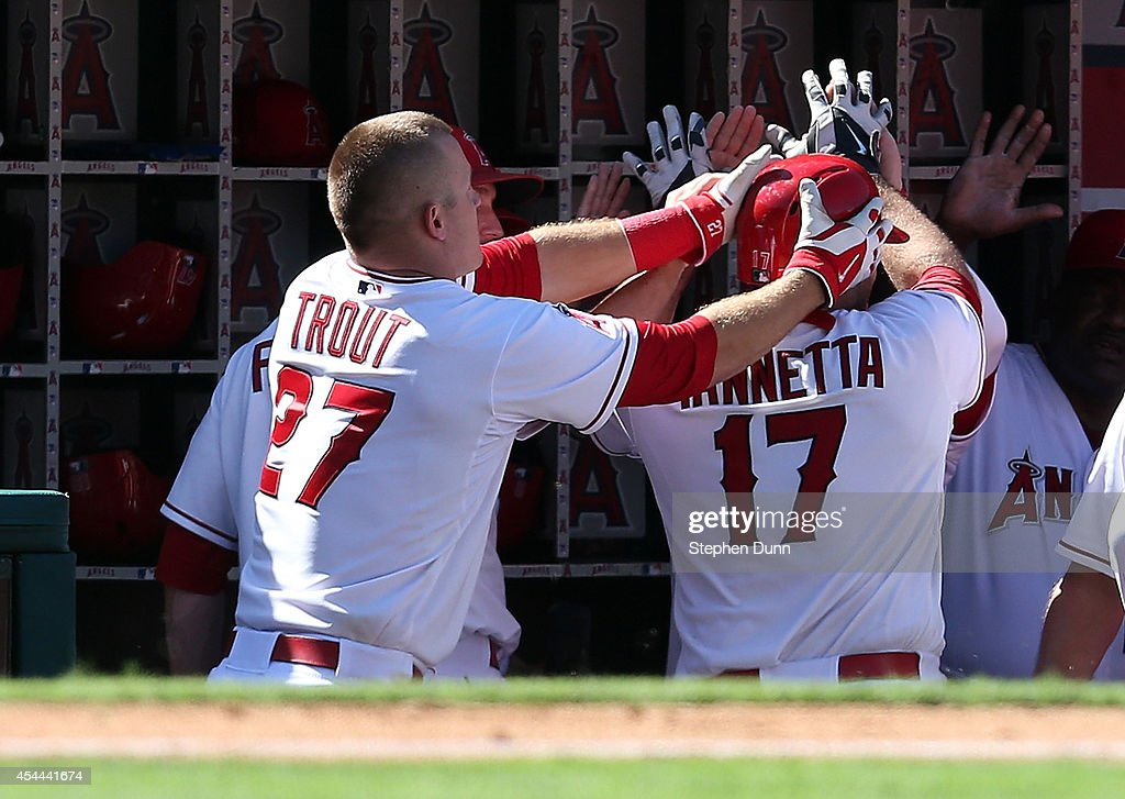 <a gi-track='captionPersonalityLinkClicked' href=/galleries/search?phrase=Mike+Trout&family=editorial&specificpeople=7091306 ng-click='$event.stopPropagation()'>Mike Trout</a> #27 of the Los Angeles Angels of Anaheim takes the helmet off of <a gi-track='captionPersonalityLinkClicked' href=/galleries/search?phrase=Chris+Iannetta&family=editorial&specificpeople=836137 ng-click='$event.stopPropagation()'>Chris Iannetta</a> #17 as the Angels celebrate in the dugout after Iannetta's solo home run in the eigth inning against the Oakland Athletics at Angel Stadium of Anaheim on August 31, 2014 in Anaheim, California. The Angels won 8-1 to complete a four game sweep.