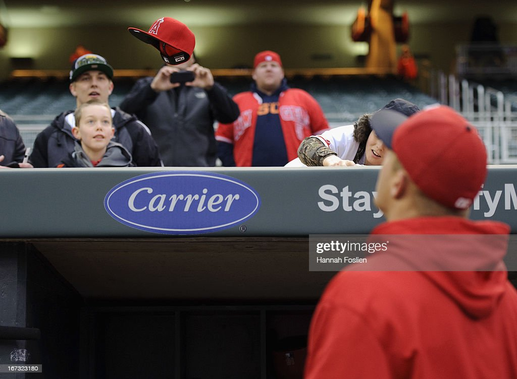 <a gi-track='captionPersonalityLinkClicked' href=/galleries/search?phrase=Mike+Trout&family=editorial&specificpeople=7091306 ng-click='$event.stopPropagation()'>Mike Trout</a> #27 of the Los Angeles Angels of Anaheim tosses a hat back to a fan after autographing it during batting practice before the game against the Minnesota Twins on April 17, 2013 at Target Field in Minneapolis, Minnesota.