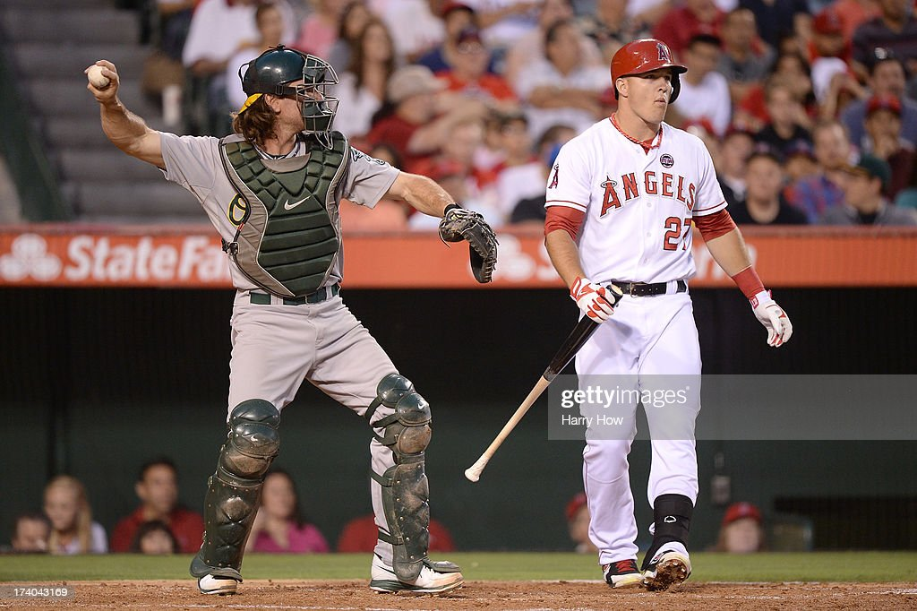 Mike Trout #27 of the Los Angeles Angels reacts to his strikeout in front of John Jaso #5 of the Oakland Athletics during the third inning at Angel Stadium of Anaheim on July 19, 2013 in Anaheim, California.