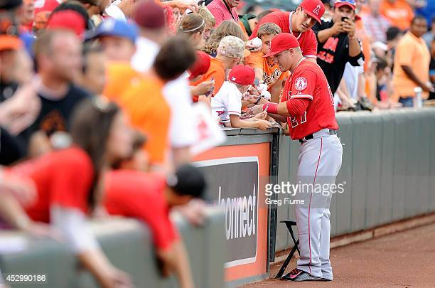 Mike Trout of the Los Angeles Angels signs autographs before the game against the Baltimore Orioles at Oriole Park at Camden Yards on July 31 2014 in...