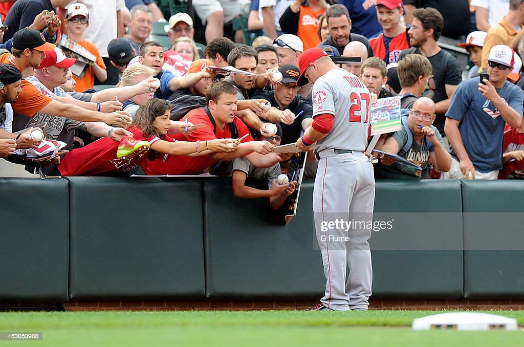 Mike Trout of the Los Angeles Angels signs autographs before the game against the Baltimore Orioles at Oriole Park at Camden Yards on July 29 2014 in...