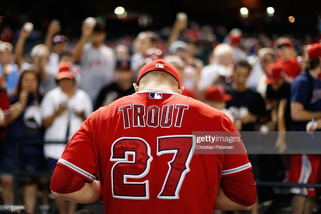 Mike Trout of the Los Angeles Angels signs autographs for fans before the MLB game against the Arizona Diamondbacks at Chase Field on June 18 2015 in...
