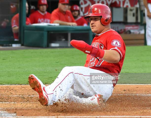 Mike Trout of the Los Angeles Angels slides into home for a run in the first inning of the game against the Washington Nationals at Angel Stadium of...