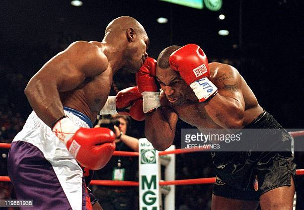 Mike Tyson protects himself from Evander Holyfield during the first round 28 June 1997 of their WBA heavyweight championship fight at the MGM Grand...