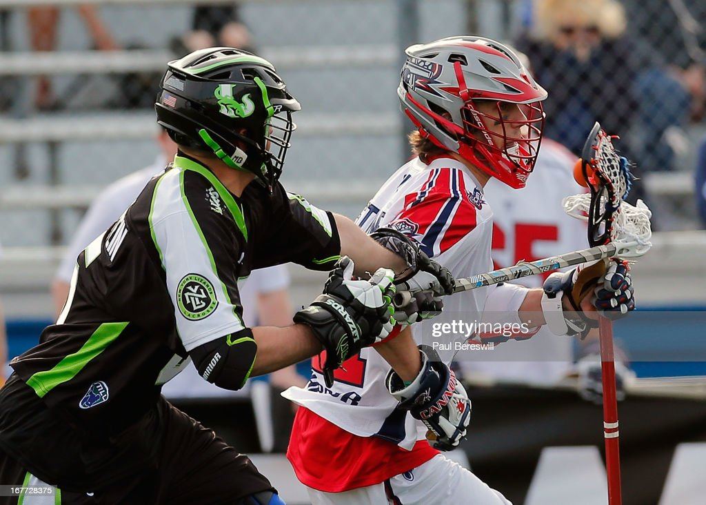 Mike Unterstein #65 of the New York Lizzards checks Mike Stone #41 of the Boston Cannons in the second half of a Major League Lacrosse game at James M. Shuart Stadium on April 28, 2013 in Hempstead, New York.