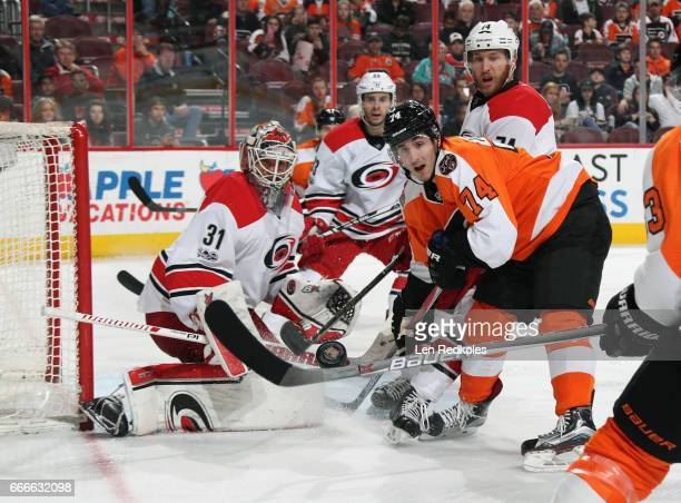 Mike Vecchione of the Philadelphia Flyers watches the airborn puck along with Eddie Lack Derek Ryan and Jaccob Slavin of the Carolina Hurricanes on...