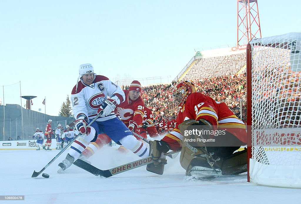 Mike Vernon #30 of the Calgary Flames Alumni makes the stop on Mike Keane #12 of the Montreal Canadiens Alumni during the Alumni game held as part of the 2011 NHL Heritage Classic festivities at McMahon Stadium on February 19, 2011 in Calgary, Alberta, Canada.