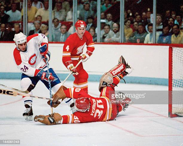 Mike Vernon of the Calgary Flames makes a diving save against Chris Chelios of the Montreal Canadiens Circa 1993 at the Montreal Forum in Montreal...