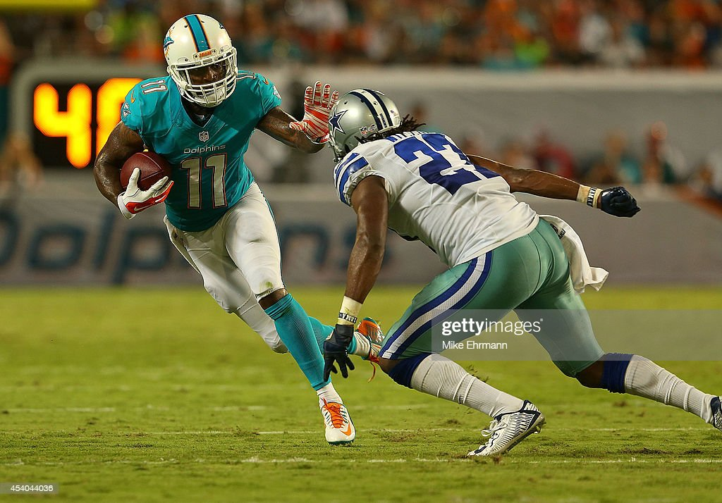 Mike Wallace of the Miami Dolphins is defended by JJ Wilcox of the Dallas Cowboys during a preseason game at Sun Life Stadium on August 23 2014 in...