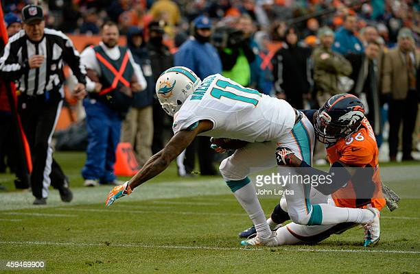 Mike Wallace of the Miami Dolphins is tackled by Kayvon Webster of the Denver Broncos The Denver Broncos played the Miami Dolphins at Sports...