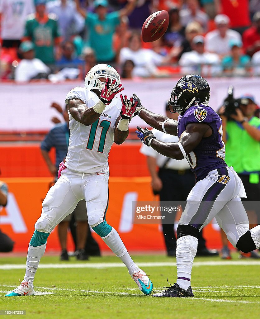 Mike Wallace #11 of the Miami Dolphins makes a catch against Matt Elam #26 of the Baltimore Ravens during a game at Sun Life Stadium on October 6, 2013 in Miami Gardens, Florida.