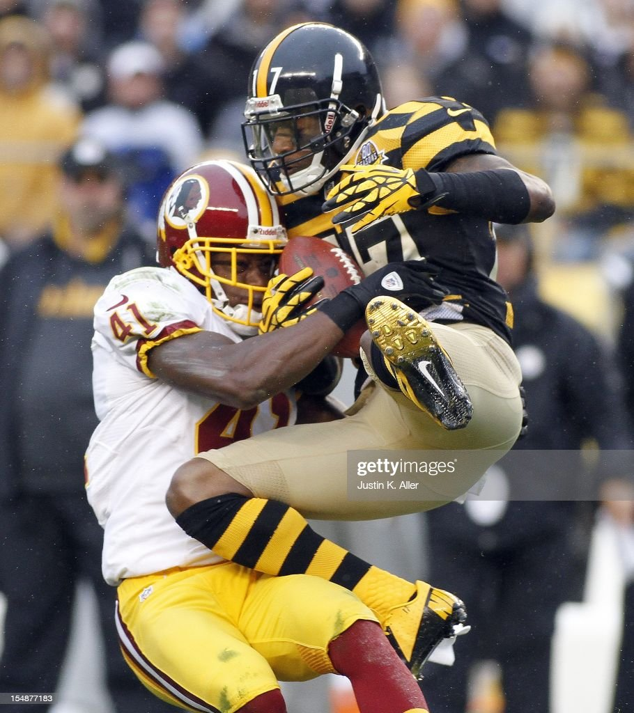Mike Wallace #17 of the Pittsburgh Steelers makes a catch and is hit by Madieu Williams #41 of the Washington Redskins during the game on October 28, 2012 at Heinz Field in Pittsburgh, Pennsylvania.
