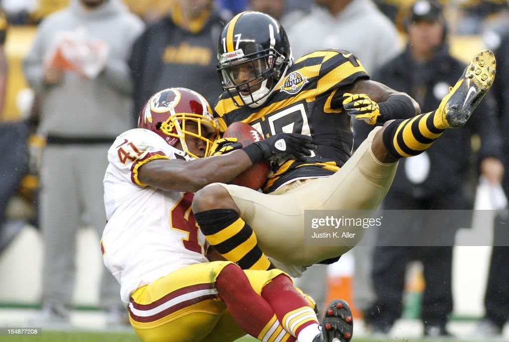 Mike Wallace #17 of the Pittsburgh Steelers makes a catch and is hit by <a gi-track='captionPersonalityLinkClicked' href=/galleries/search?phrase=Madieu+Williams&family=editorial&specificpeople=221000 ng-click='$event.stopPropagation()'>Madieu Williams</a> #41 of the Washington Redskins during the game on October 28, 2012 at Heinz Field in Pittsburgh, Pennsylvania.