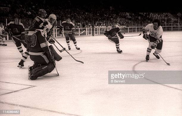 Mike Walton of the Minnesota Fighting Saints shoots on goalie Richard Brodeur of the Quebec Nordiques as his teammate Francois Lacombe defends the...