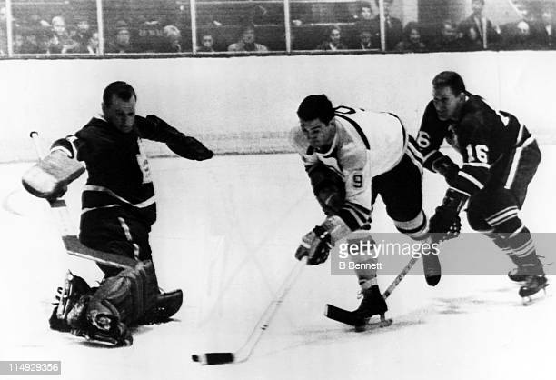 Mike Walton of the Toronto Maple Leafs attempts to stop John Bucyk of the Boston Bruins from shooting the puck as goalie Johnny Bower of the Maple...