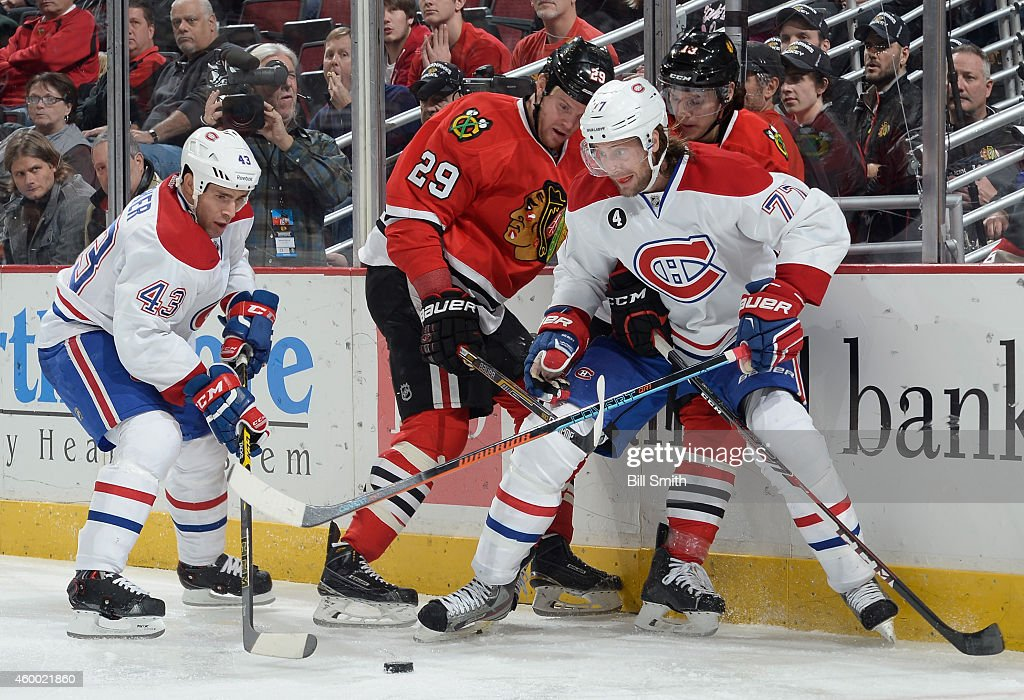 Mike Weaver and Tom Gilbert of the Montreal Canadiens battle for the puck with Bryan Bickell and Daniel Carcillo of the Chicago Blackhawks during the...