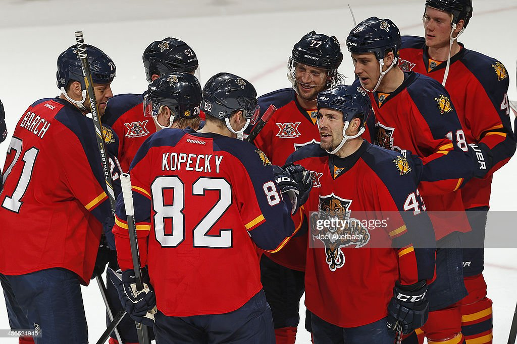Mike Weaver #43 congratulates Tomas Kopecky #82 of the Florida Panthers after he scored the game winning goal in the shootout against the Washington Capitals at the BB&T Center on December 13, 2013 in Sunrise, Florida. The Panthers defeated the Capitals 3-2 in a shootout.
