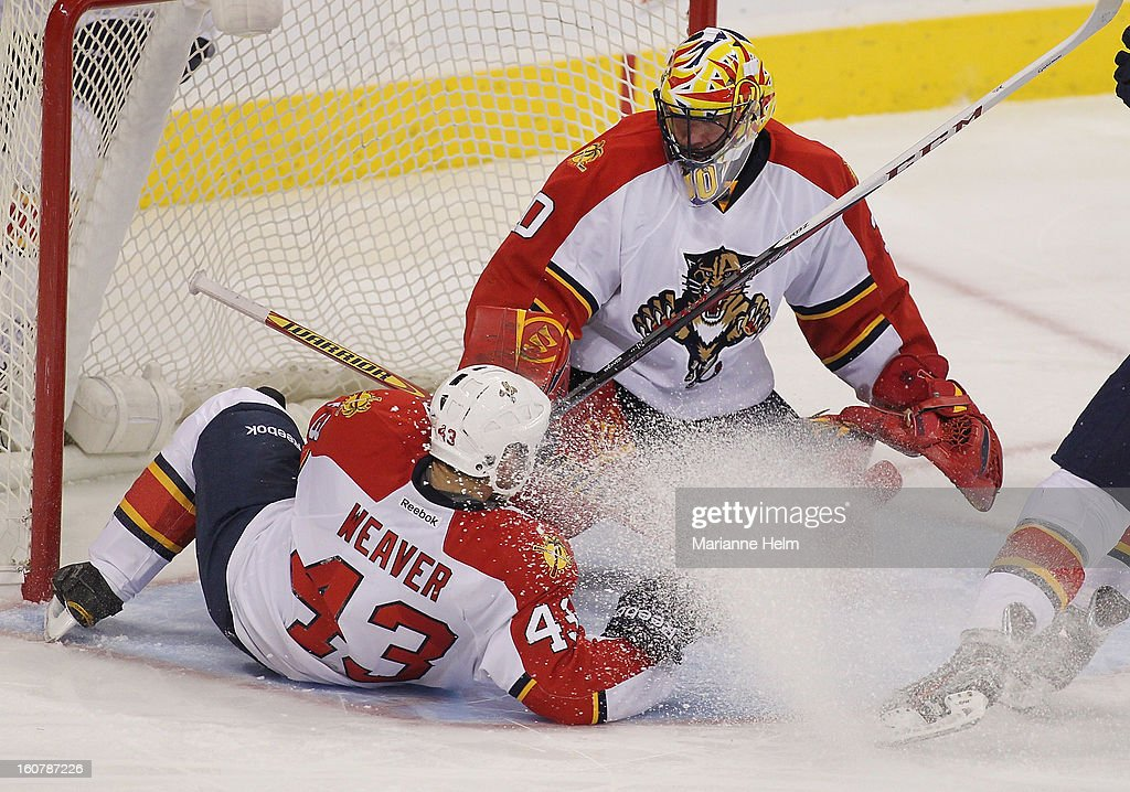 Mike Weaver #43 gets a face full of ice as he lies on his back trying to help Scott Clemmensen #30 of the Florida Panthers protect the net in a game against the Winnipeg Jets tries to find the puck during NHL action on February 5, 2013 at the MTS Centre in Winnipeg, Manitoba, Canada.