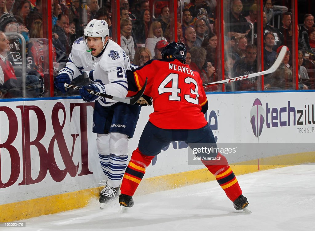 Mike Weaver #43 of the Florida Panthers checks James van Riemsdyk #21 of the Toronto Maple Leafs into the boars behind the net at the BB&T Center on February 18, 2013 in Sunrise, Florida.