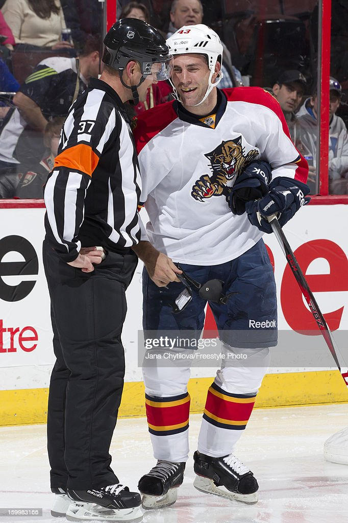 Mike Weaver #43 of the Florida Panthers holds a broken skate protector as he chats with referee Kyle Rehman #37 during an NHL game against the Ottawa Senators at Scotiabank Place on January 21, 2013 in Ottawa, Ontario, Canada.