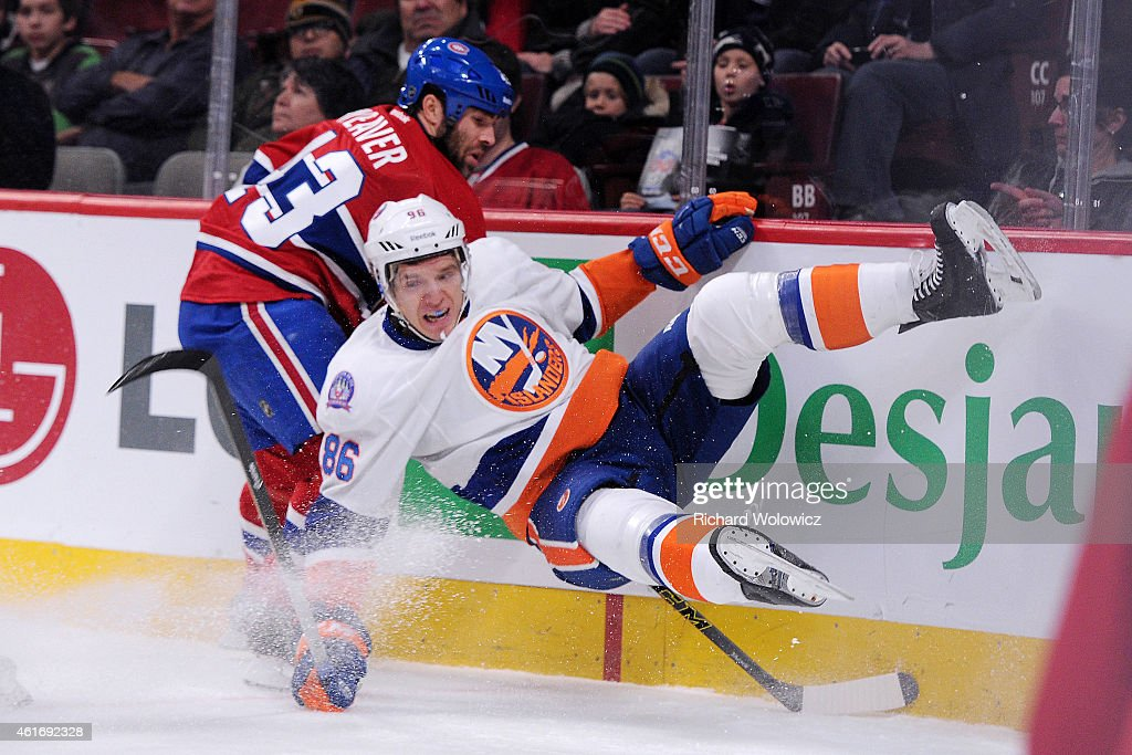 Mike Weaver of the Montreal Canadiens body checks Nikolay Kulemin of the New York Islanders during the NHL game at the Bell Centre on January 17 2015...
