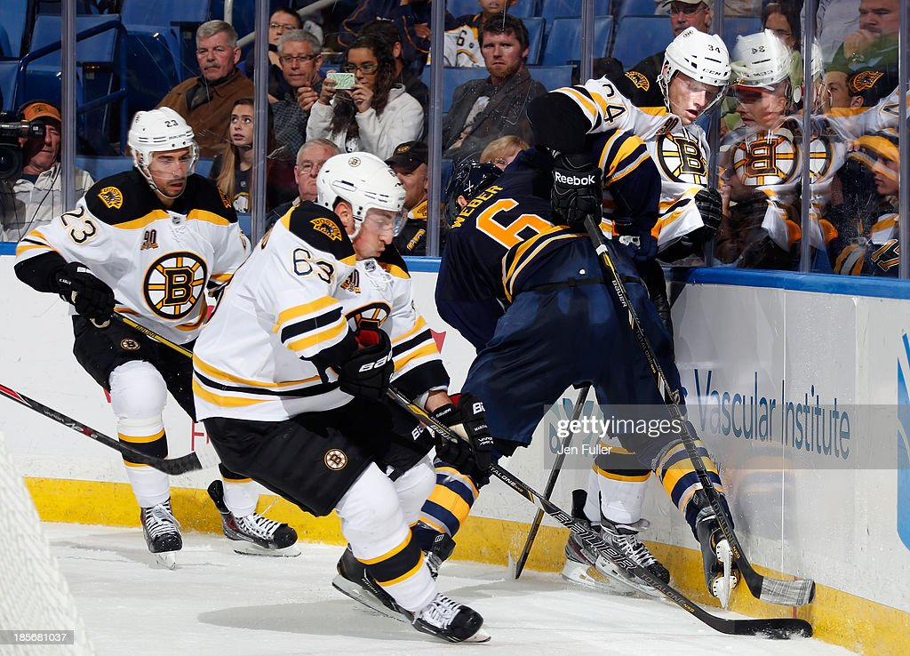 Mike Weber #6 of the Buffalo Sabres checks Carl Soderberg #34 of the Boston Bruins as Brad Marchand #63 of Boston controls the puck at First Niagara Center on October 23, 2013 in Buffalo, New York. Boston defeated Buffalo 5-2.