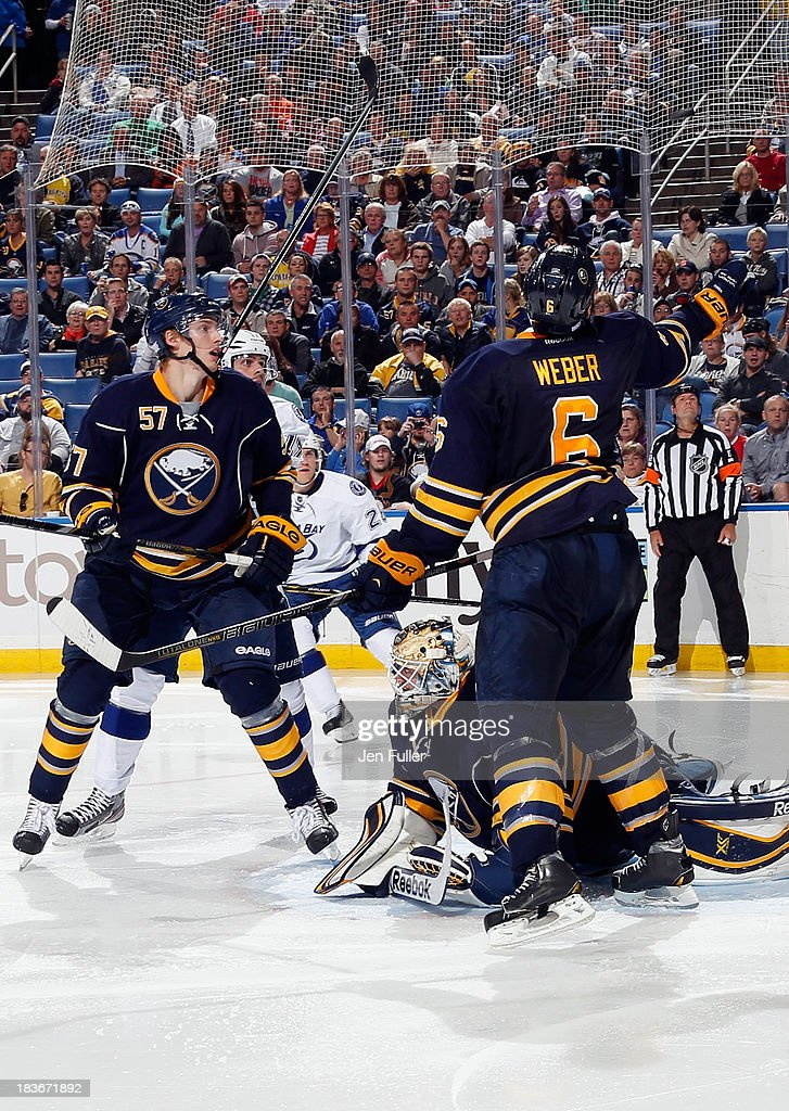 Mike Weber #6 of the Buffalo Sabres reaches for the puck above him while alongside teammates <a gi-track='captionPersonalityLinkClicked' href=/galleries/search?phrase=Tyler+Myers&family=editorial&specificpeople=4595080 ng-click='$event.stopPropagation()'>Tyler Myers</a> #57 and <a gi-track='captionPersonalityLinkClicked' href=/galleries/search?phrase=Jhonas+Enroth&family=editorial&specificpeople=570456 ng-click='$event.stopPropagation()'>Jhonas Enroth</a> #1 in their game against the Tampa Bay Lightning at First Niagara Center on October 8, 2013 in Buffalo, New York. Tampa defeated Buffalo 3-2.