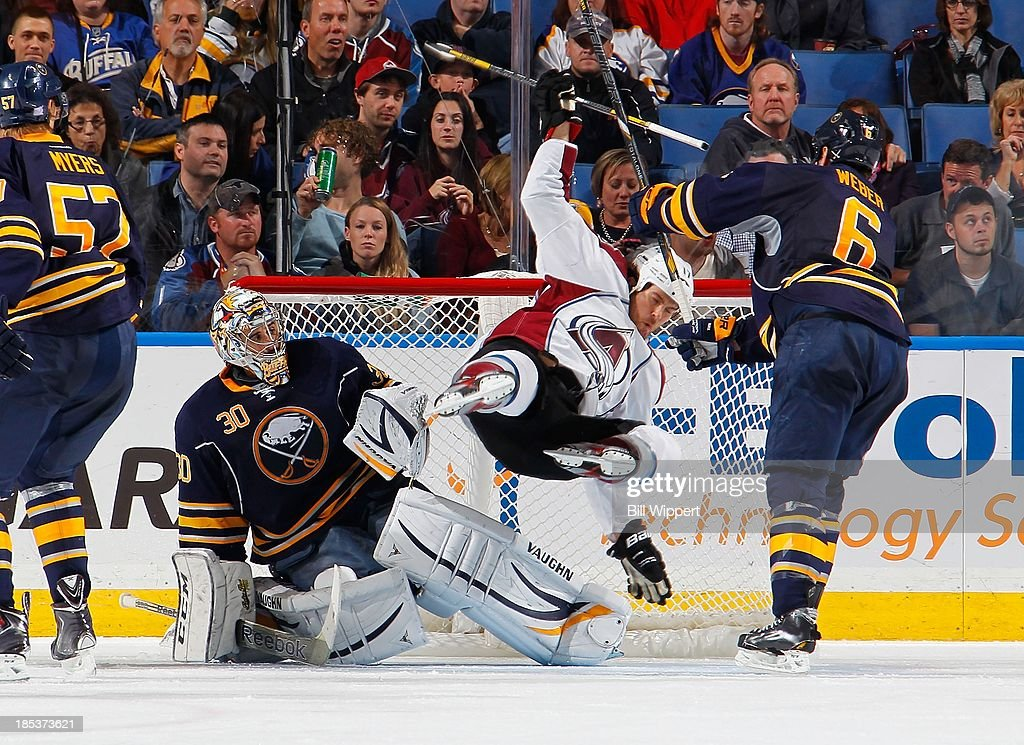 Mike Weber #6 of the Buffalo Sabres upends Steve Downie #17 of the Colorado Avalanche alongside Sabres goaltender Ryan Miller #30 on October 19, 2013 at the First Niagara Center in Buffalo, New York. Weber received an interference penalty on the play.