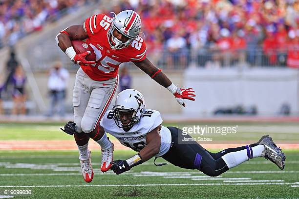 Mike Weber of the Ohio State Buckeyes eludes a tackle attempt from Godwin Igwebuike of the Northwestern Wildcats on his way to a 23yard touchdown run...