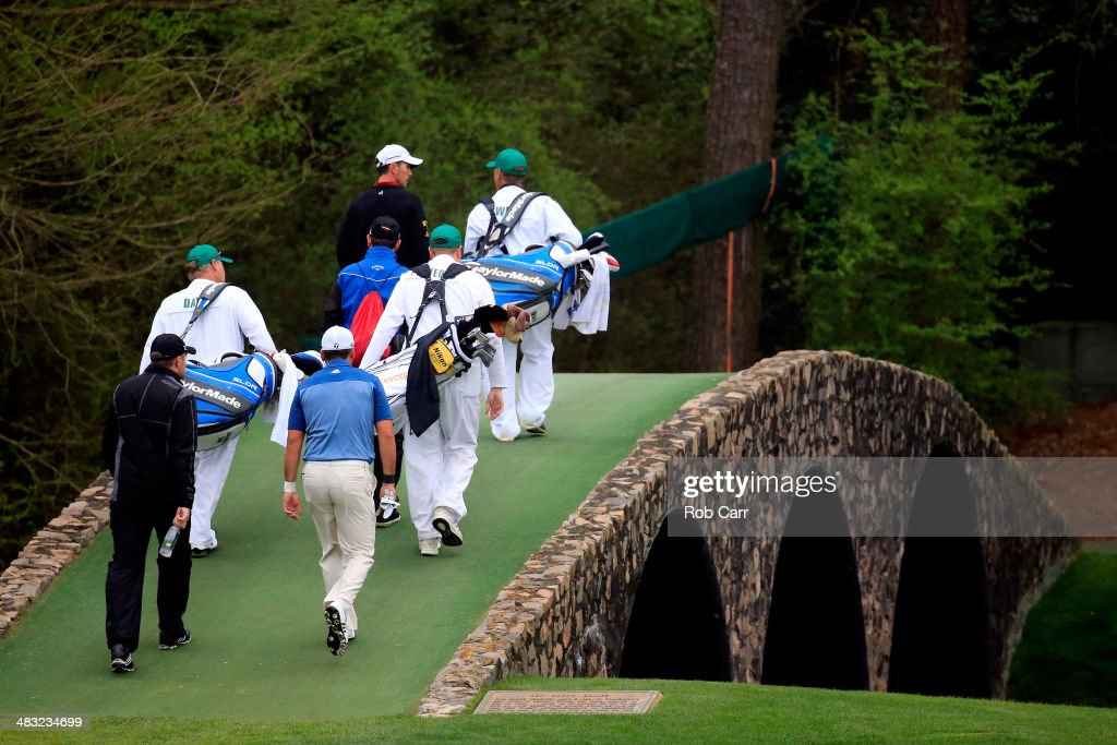 <a gi-track='captionPersonalityLinkClicked' href=/galleries/search?phrase=Mike+Weir&family=editorial&specificpeople=182540 ng-click='$event.stopPropagation()'>Mike Weir</a> of Canada, Garrick Porteous of England and <a gi-track='captionPersonalityLinkClicked' href=/galleries/search?phrase=Jason+Day+-+Golfer&family=editorial&specificpeople=4534484 ng-click='$event.stopPropagation()'>Jason Day</a> of Australia walk over Hogan's Bridge on the 12th hole with their caddies during a practice round prior to the start of the 2014 Masters Tournament at Augusta National Golf Club on April 7, 2014 in Augusta, Georgia.