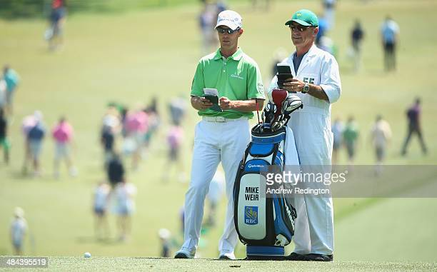 Mike Weir of Canada waits on the first fairway alongside caddie Bill Heim during the third round of the 2014 Masters Tournament at Augusta National...