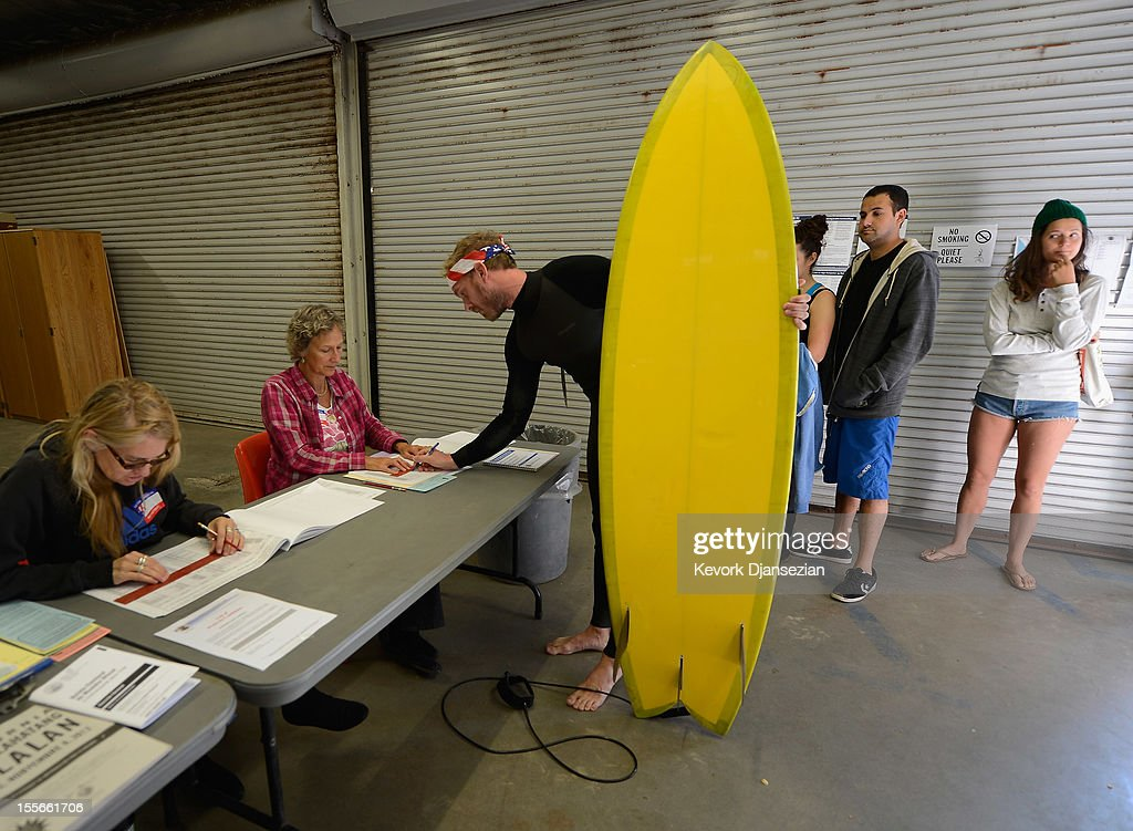 Mike Wigart (2nd L), 30, picks up his ballot at a polling station in the garage of the Los Angeles County lifeguard headquarters on November 6, 2012 in Los Angeles, California. Californians will cast ballots in dozens of tight races including Gov. Jerry Brown's tax plan, abolishing the death penalty, easing the state's strict 'three strikes' sentencing law and also in the Presidential race between Democratic President Barack Obama and Republican candidate Mitt Romney.