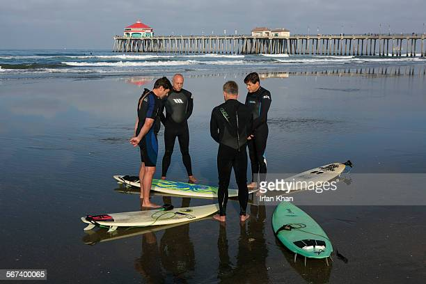 MAY 31 2014 Mike Wilde left Brian Olsen Mark Dale and David Bremmer offer a prayer before they go for surfing Huntington Beach on Saturday morning