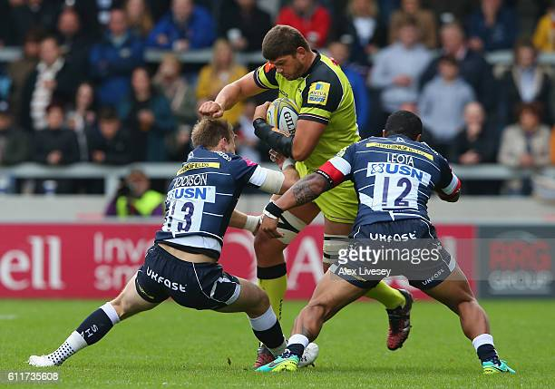 Mike Williams of Leicester Tigers is tackled by Will Addison and Johnny Leota of Sale Sharks during the Aviva Premiership match between Sale Sharks...