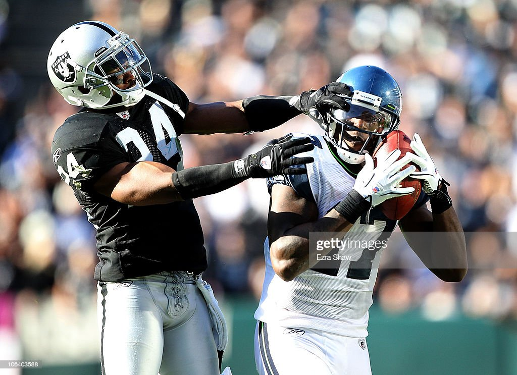 Mike Williams #17 of the Seattle Seahawks catches the ball while defended by Michael Huff #24 of the Oakland Raiders at Oakland-Alameda County Coliseum on October 31, 2010 in Oakland, California.