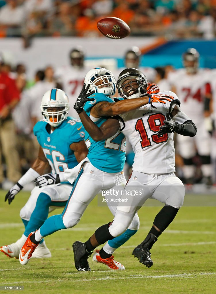 Mike Williams #19 of the Tampa Bay Buccaneers is unable to hold onto the ball while being defended by Jamar Taylor #22 of the Miami Dolphins during a preseason game on August 24, 2013 at Sun Life Stadium in Miami Gardens, Florida. The Buccaneers defeated the Dolphins 17-16.