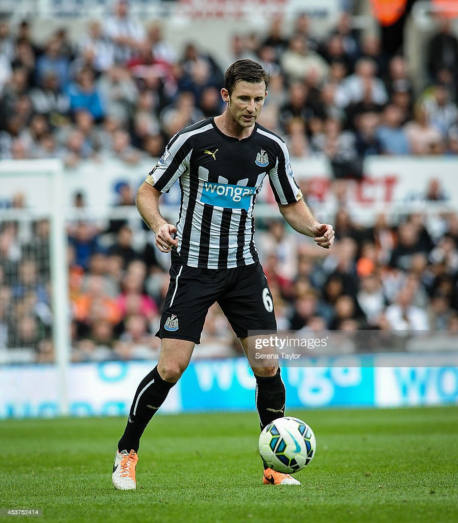 Mike Williamson of Newcsatle runs with the ball during the Barclays Premier League match between Newcastle United and Manchester City at St.James' Park on August 17, 2014, in Newcastle upon Tyne, England.