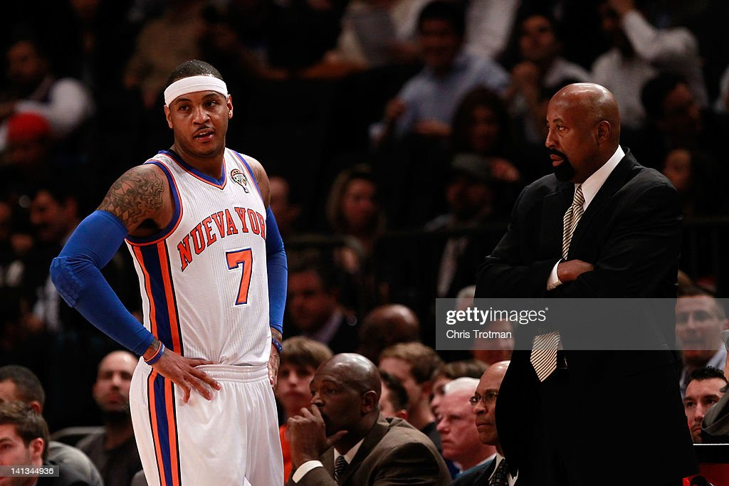 Mike Woodson the interim head coach of the New York Knicks looks on with Carmelo Anthony of the New York Knicks during the game against the Portland...
