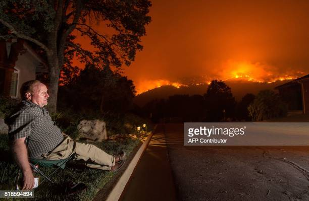 TOPSHOT Mike Wright sits in a lawn chair at his home as flames from the Detwiler fire approach the town of Mariposa California on July 18 2017 The...