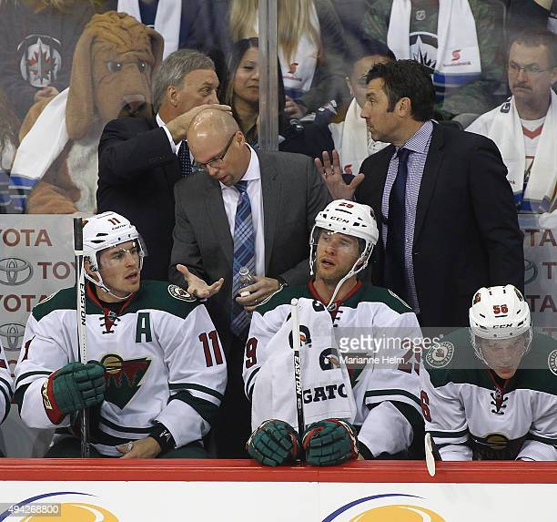Mike Yeo head coach of the Minnesota Wild talks to Zach Parise on the bench in first period action in an NHL game against the Winnipeg Jets at the...