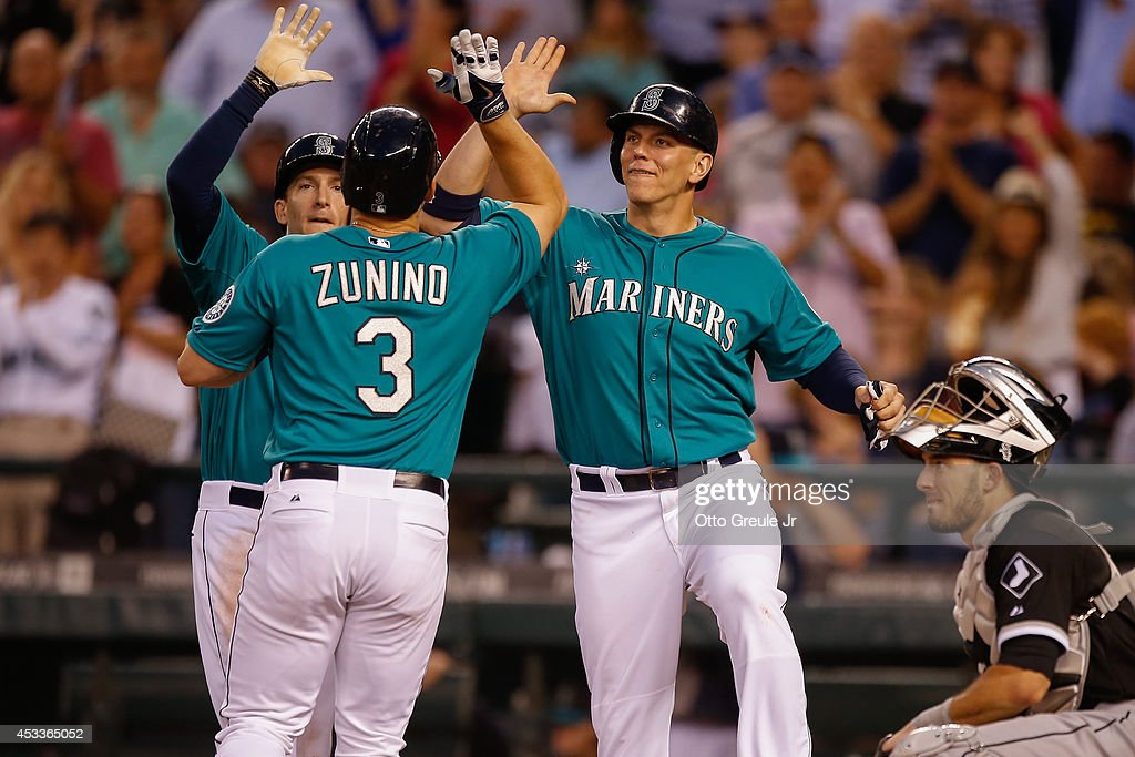 <a gi-track='captionPersonalityLinkClicked' href=/galleries/search?phrase=Mike+Zunino&family=editorial&specificpeople=6803368 ng-click='$event.stopPropagation()'>Mike Zunino</a> #3 of the Seattle Mariners is congratulated by <a gi-track='captionPersonalityLinkClicked' href=/galleries/search?phrase=Chris+Denorfia&family=editorial&specificpeople=702417 ng-click='$event.stopPropagation()'>Chris Denorfia</a> #28 (L) and Logan Morrison #20 after hitting a three-run homer in the fifth inning against the Chicago White Sox at Safeco Field on August 8, 2014 in Seattle, Washington. Catcher Adrian Nieto #17 looks on.