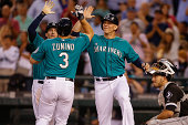 Mike Zunino of the Seattle Mariners is congratulated by Chris Denorfia and Logan Morrison after hitting a threerun homer in the fifth inning against...